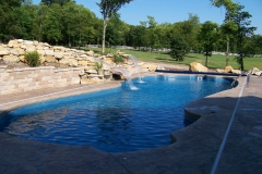 Full view of fiberglass pool with slide and rock landscaping.
