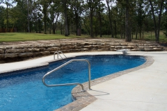 Fiberglass Pool with diving board and rock wall.