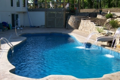 Family size fiberglass pool with water falls and slide.
