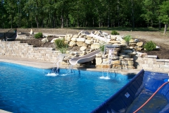 Fiberglass pool with slide and rocks.