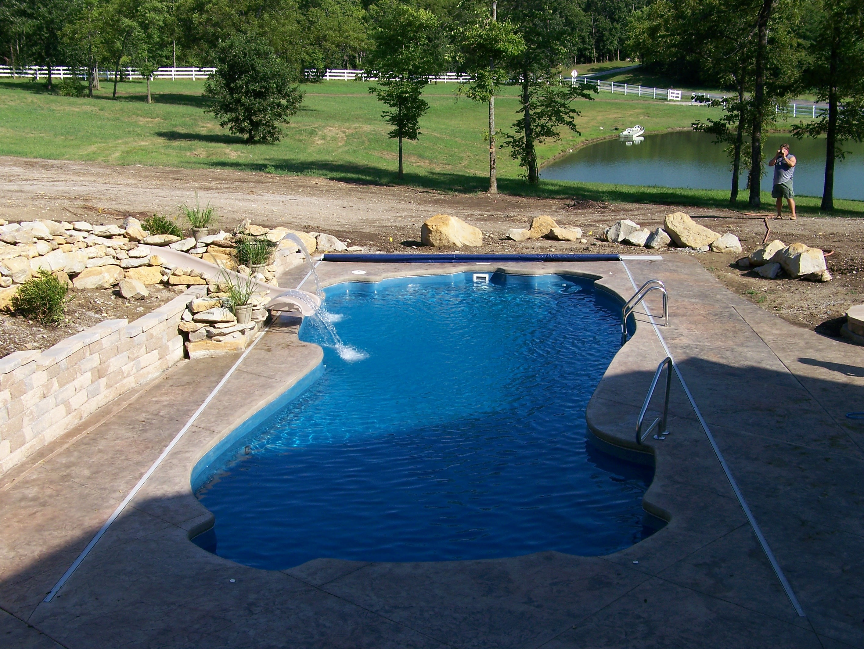 Sideview of fiberglass pool with slide.