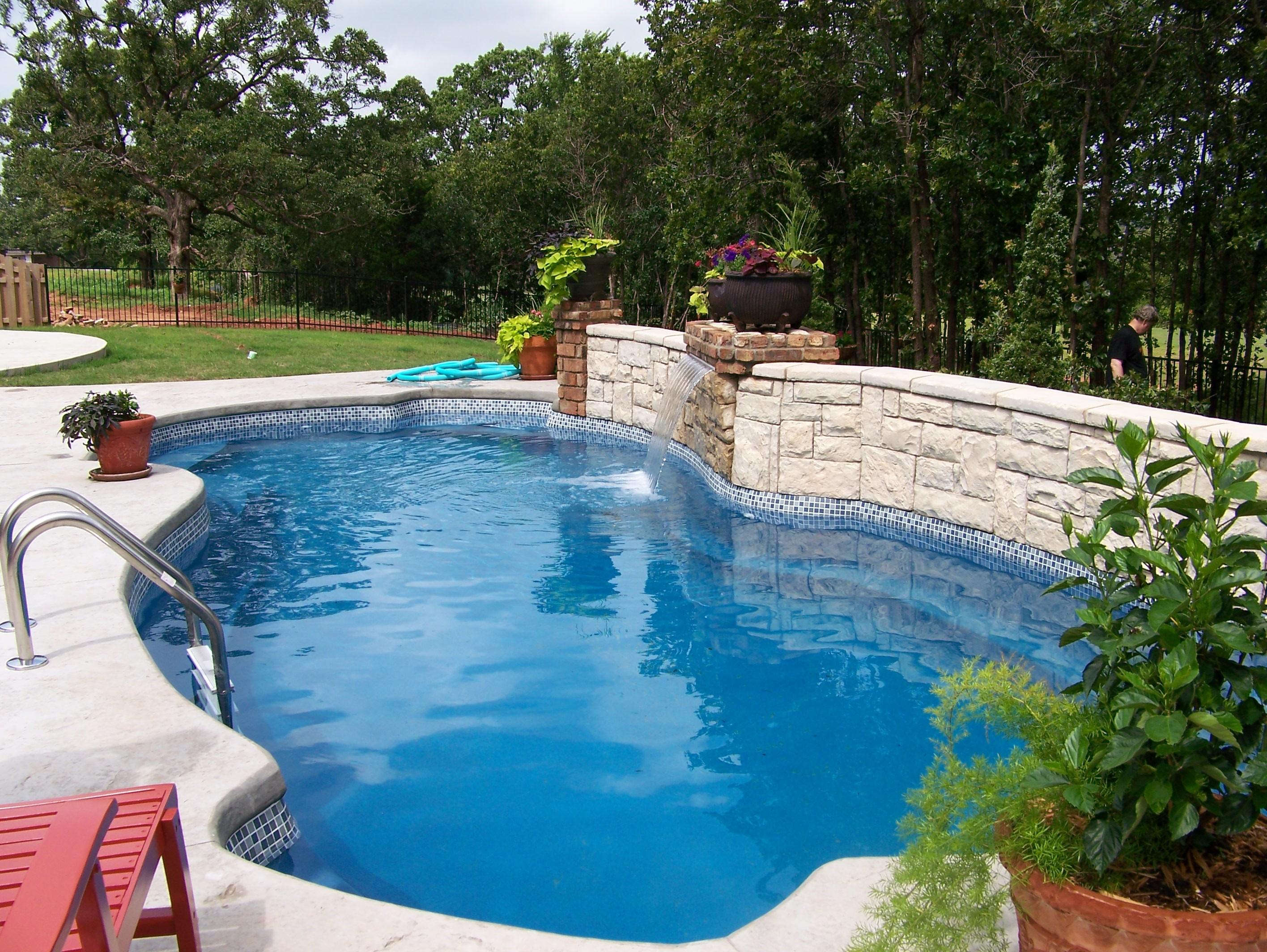 Elegant landscaping around the inground swimming pool.
