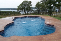 Stunning fiberglass pool with a lake backdrop and an elegant water fountain.