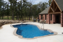 Fiberglass pool on a large patio with plenty of room for entertaining.